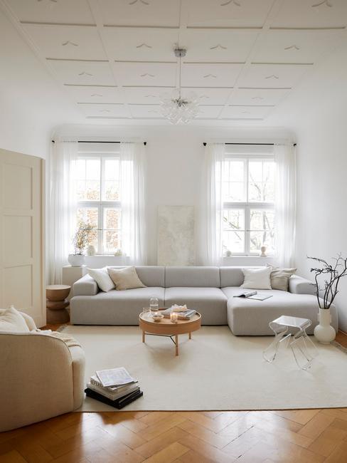 Jasny salon w stylu japandi z białymi ścianami, szarą sofą, małym drewnianym stoliczkiem oraz kompozycją w wazonie