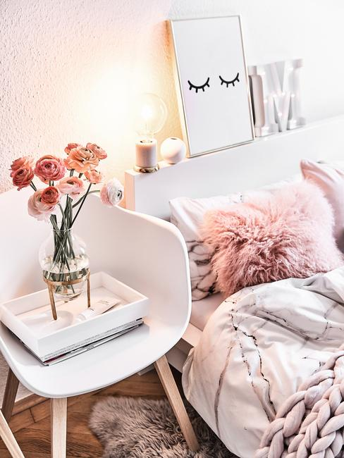 Zbliżenie na fragment łóżka z różowymi poduszkami oraz białe krzesło z wazonem kwiatów i dekoracje