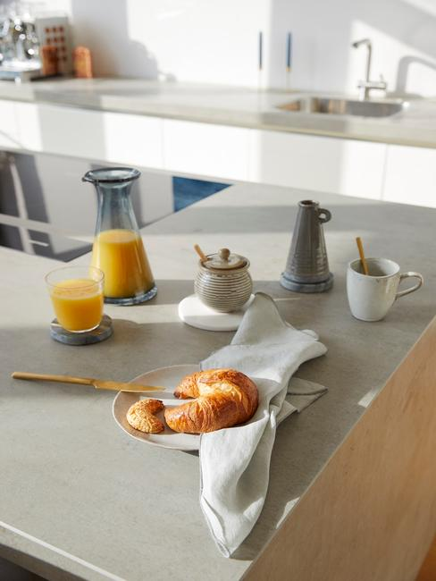 Białą kuchnia z granitowym blatem roboczym oraz wyspą kuchenną z zastawą śniadaniową