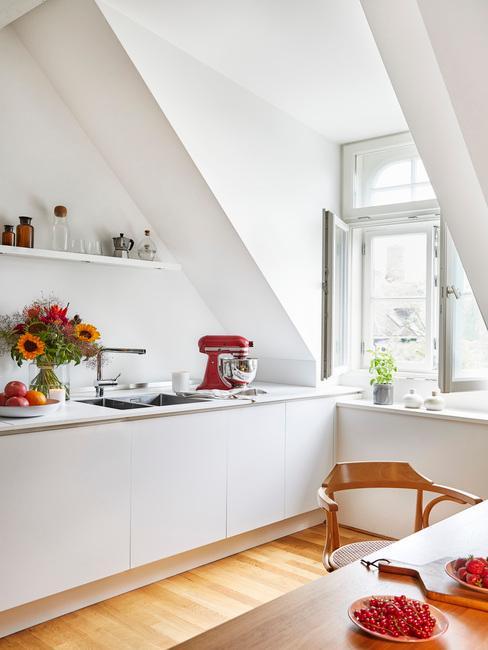 Biała kuchnia w stlu scandi na poddaszu z czerwonymi akcesoriami kuchennymi