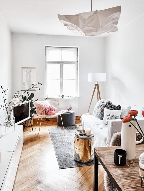Kawalerk urządzona w stylu skandynawskim z sofą, dywanem, lampą, białym regalem i drewnianym stołem