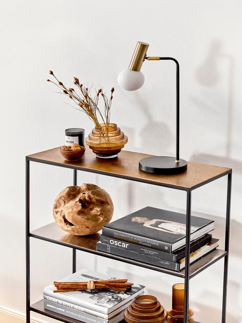 Zbliżenie na metalową półkę z wazonem z suszonymi kwiatami, lampą, książkami
