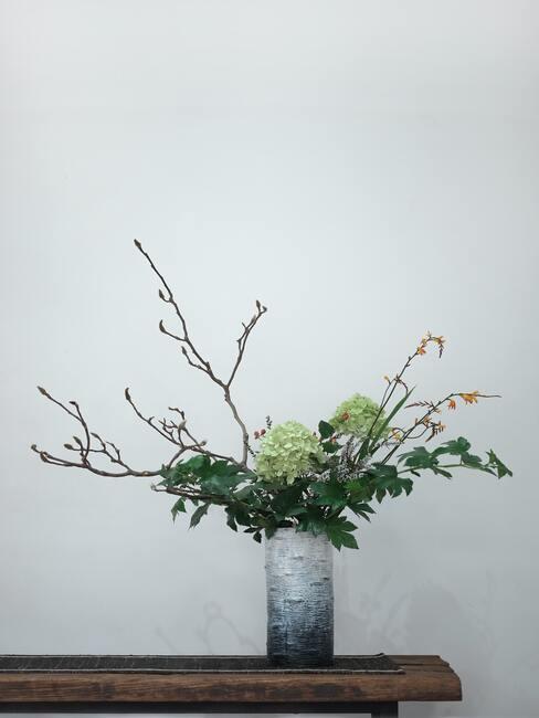 Zielone kwiaty ułożone w bukiet w stylu ikebana