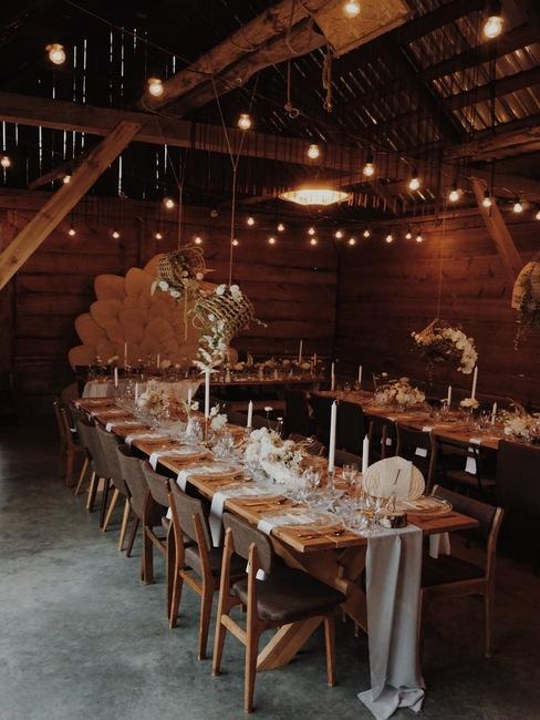 Weselne stoły z naturalnymi dekoracjami w weselnej stodole Folwarku Ruchenka