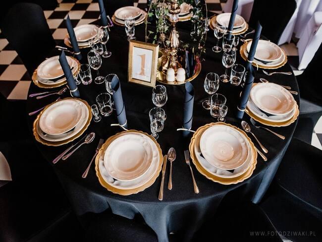 okrągły stół z czarnym obrusem i białą zastawą na białoczarnej podłodze w szachownicę
