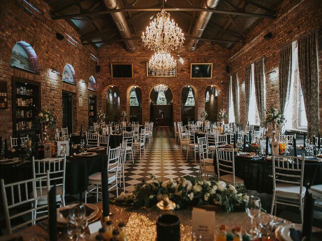 pofabryczna sala weselna z cegły ze stolikami nakrytymi czarnymi obrusami przy szarych drewnianych krzesłach