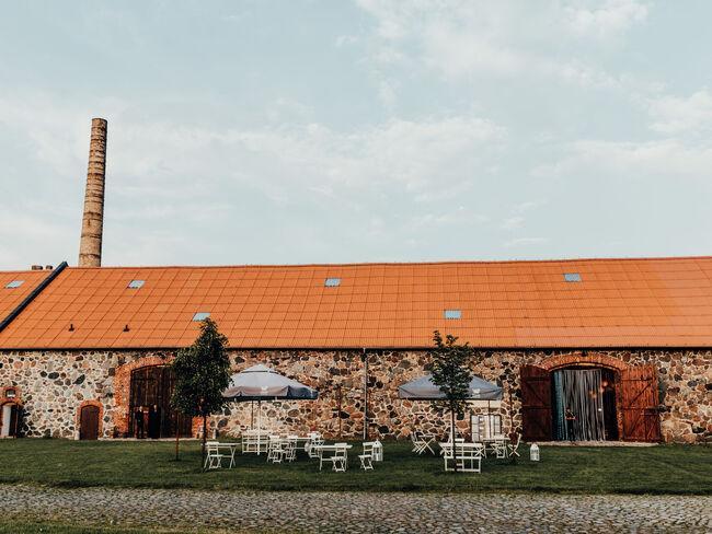 sala weselna z czerwonym dachem z białymi stolikami na zewnątrz