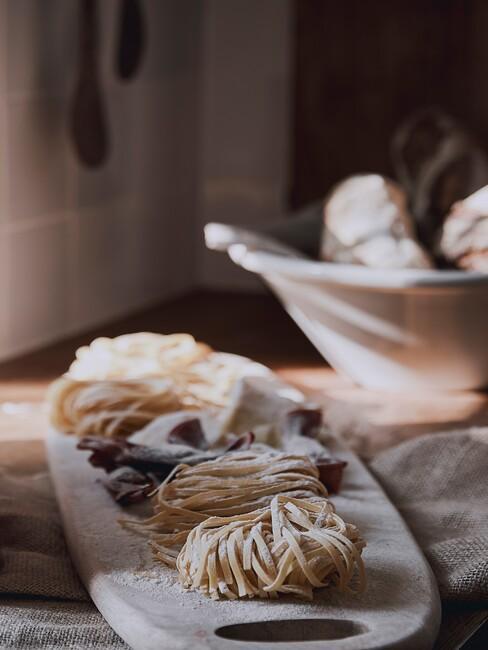 domowy makaron na drewnianej desce w kuchni obok miski