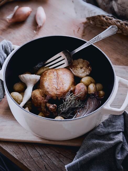 Pieczony kurczak z warzywami z beżowym, żeliwnym garnku na drewnianym blacie