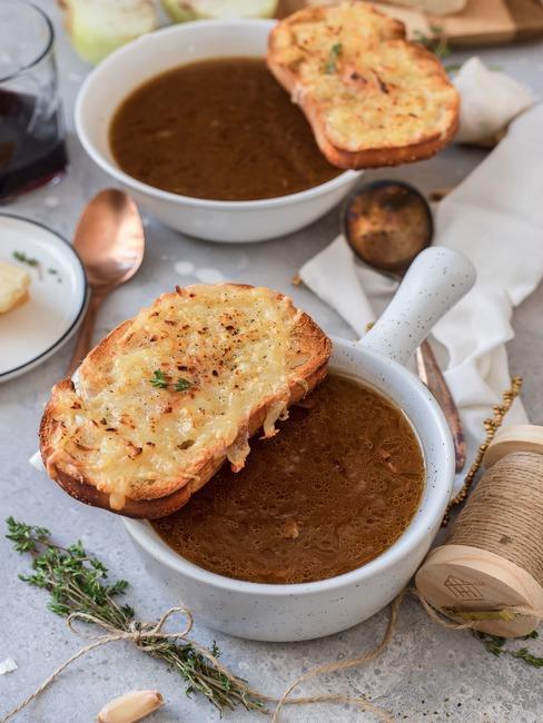 Francuska zupa cebulowa w białych miseczkach z grzanką
