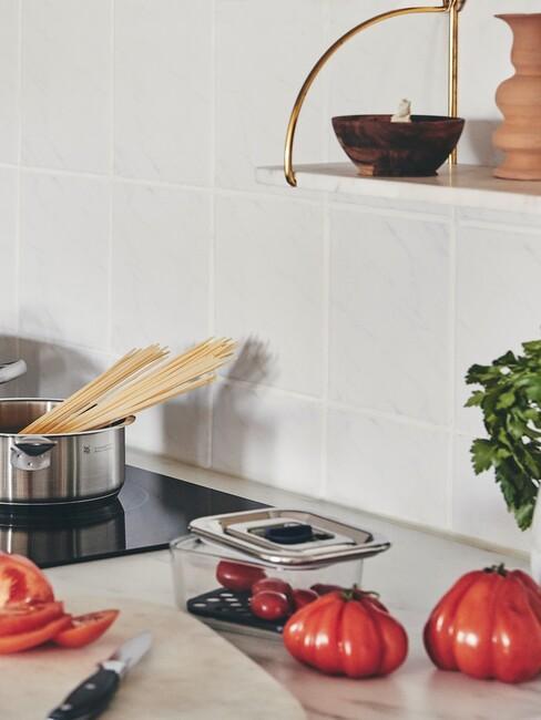 Zbliżenie na biały blat w kuchni z pudełkiem, pomidorami oraz kuchnią indukcyjną z garnkiem
