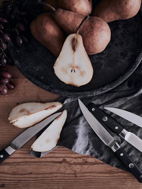 Czarny talerz z gruszkami na drewnianym blacie z zestawem noży