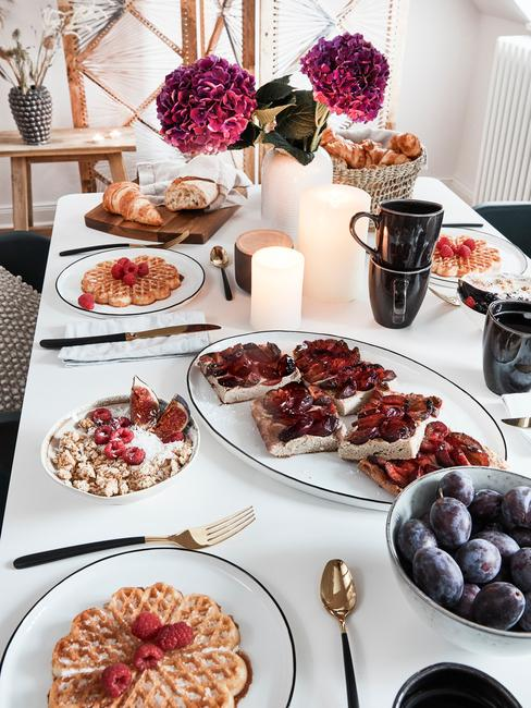 Zastawiony biały stół z zestawem białych talerzy, talerzami do serwowania oraz czarnymi kubkami na brunch