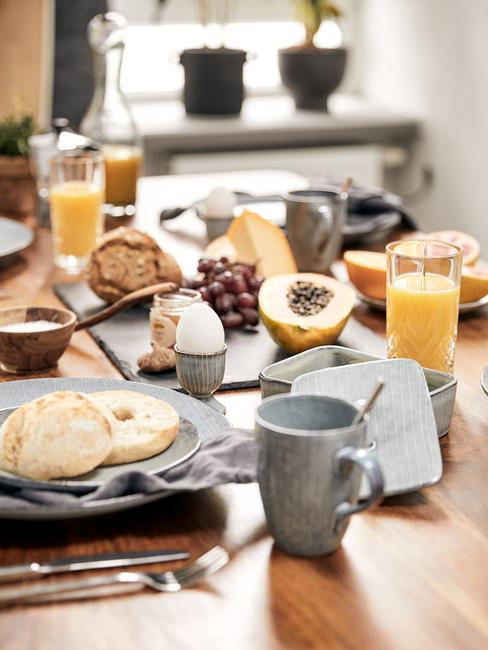 Zbliżenie na drewniany stół z zastawą stołową w stylu skandynawskim oraz jedzeniem na brunch