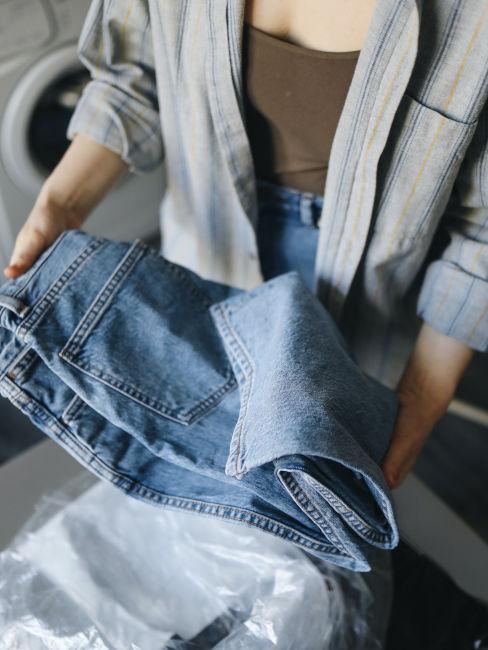Kobieta składająca jasne niebieskie jeansy