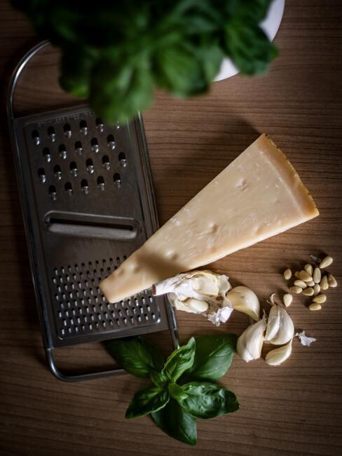 Ser włoski, tarka, czosnek i bazylia ułożone na drewnianym blacie