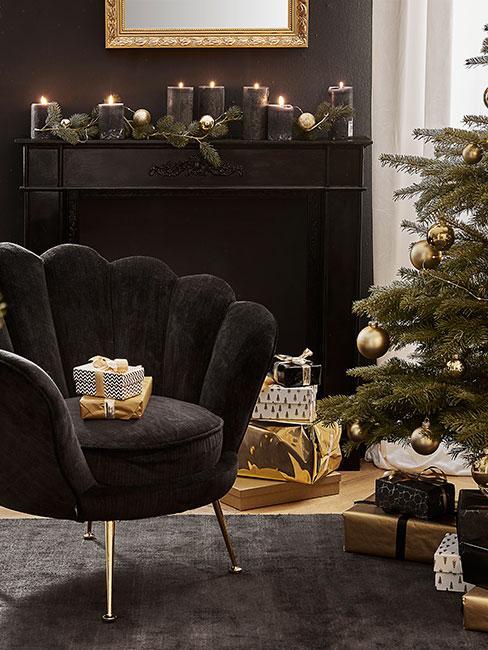 Czarny fotel koktajlowy z aksamitu w salonie przy czarnym kominku przy choince ze złotymi bombkami na czarnym dywanie