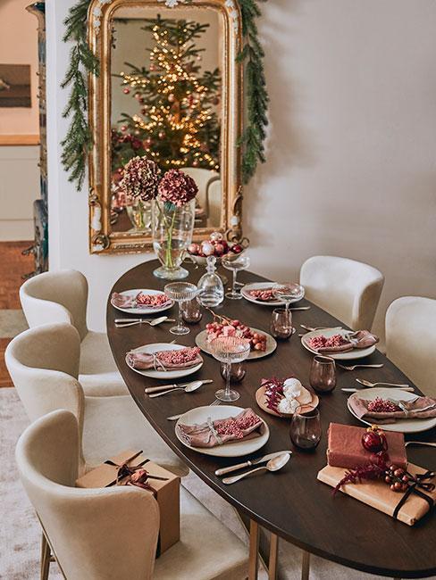 Owalny drewniany stół w jadalni z krzesłami z beżowego aksamity udekorowany na Wigilię