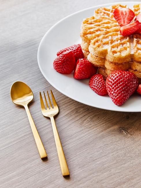 Biały talerz w goframi w kształcie serca z truskawkami na drewnianym stole obok złotych sztućcy