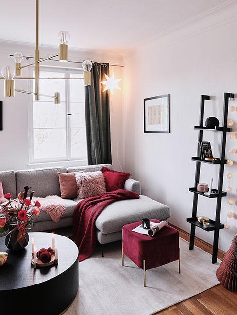 Salon z szarą sofą narożną i bordowymi tekstyliami udekorowany na święta