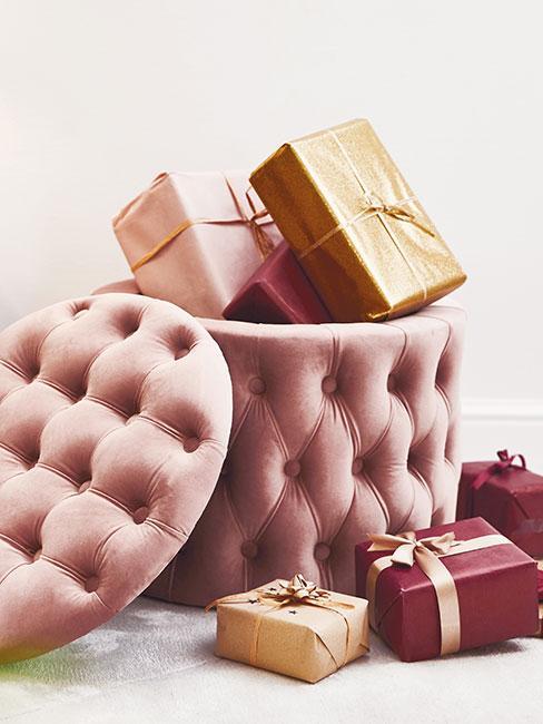 pikowany różowy puf z funkcją przechowywania wypełniony złotymi i czerwonymi prezentami