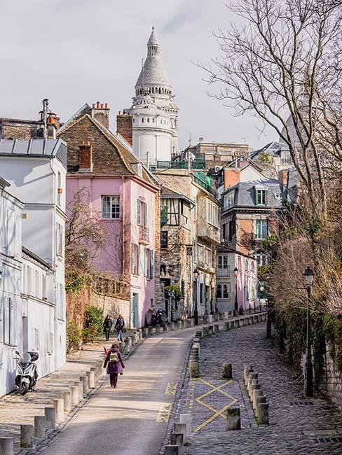 Stroma uliczka z różową kamienicą w Montmartre w Paryżu
