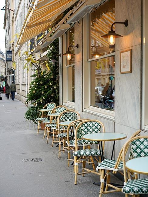 Paryska kawiarnia z zielonymi krzesłami z plecionki wiedeńskiej na zewnątrz