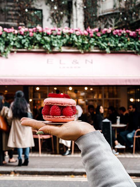 Różowy makaronik przekładany mailinami na tle okwieconej kawiarni w Paryżu