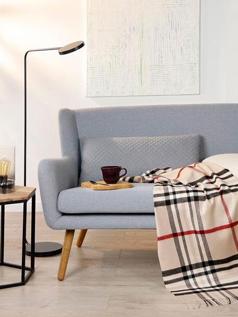 szara sofa w salonie w stylu skandynawskim z pledem w jasną kratę