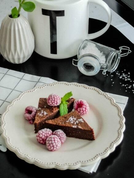 Bezglutenowe brownie z fior de sal na białym, deserowym talerzu na ściereczce w kratę