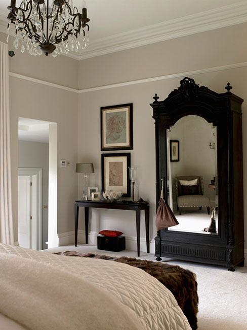 sypialnia drewnianą szafą w stylu wiktoriańską i dekoracyjnym żyrandolem