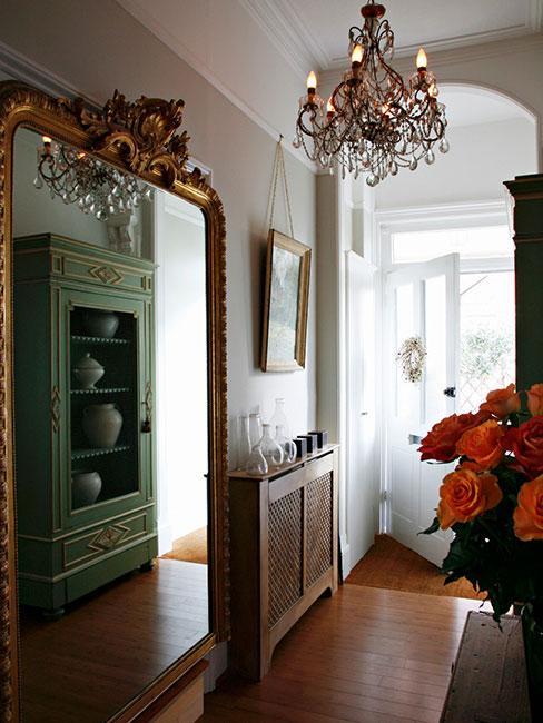 Przedpokój z dużym lustrem barokowym i kryształowym żyrandolem