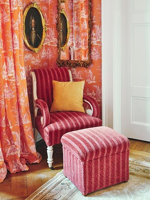 różowym tapicerowany fotel w pasy z podnóżkiem na tle tapety i zasłony w pomarańczowe wzory