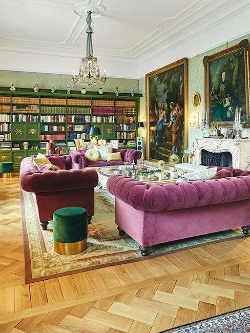 duży salon z różwymi sofami Chesterfield, dużymi portretami i okazałą biblioteczką z zielonego drewna