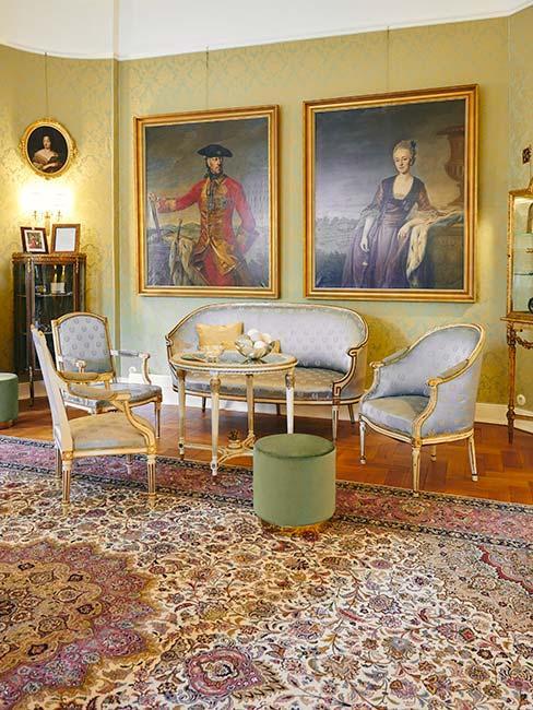 salon z szrą sofą i fotelami w barokowym stylu, z dużym dywanem vintage