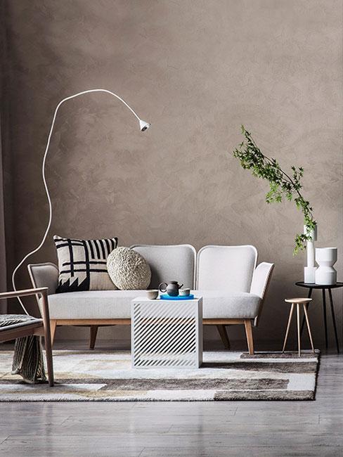 Salon z jasną sofą na tle szarej ściany w stylu minimalistycznym