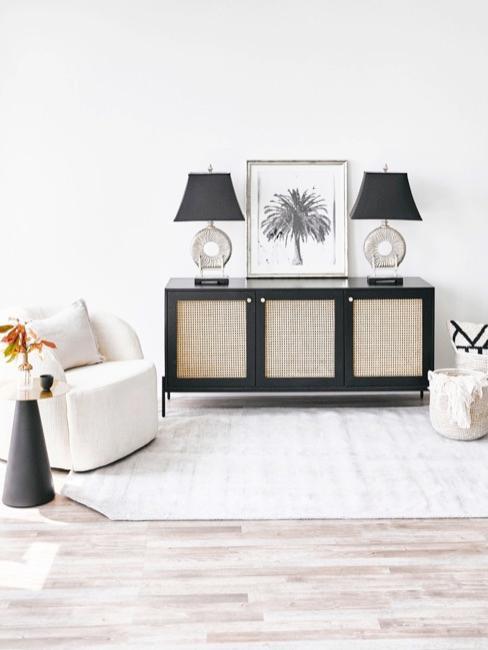 Jasny salon z białym tapicerowanym fotelem i czarną komodą z plecionką wiedeńską w stylu japońskim