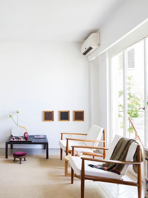 Jasny minimalistyczna salon z beżowymi fotelami z drewnianymi oparciami i niską komodą