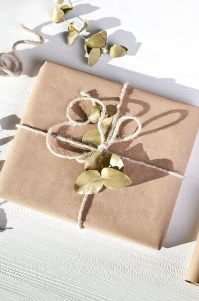 Prezent zapakowany w ekologiczny, brązowy papier, sznurek i eukaliptus
