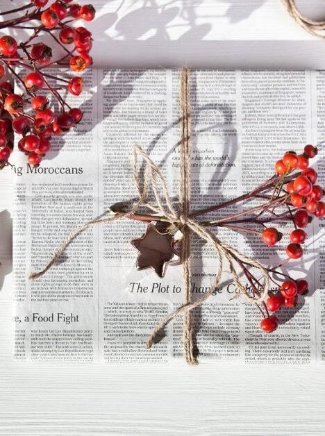 Prezent opakowany w gazetę, ze sznurkiem z juty, gałązką róży oraz foremką na ciasteczko jako dekoracja