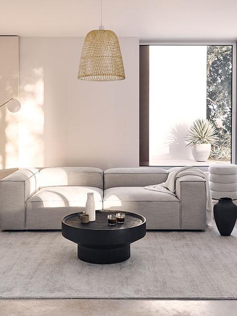 Szara sofa modułowa z niskim okgrągłym czarnym stołem kawowoym z drewna w jasnym salonie