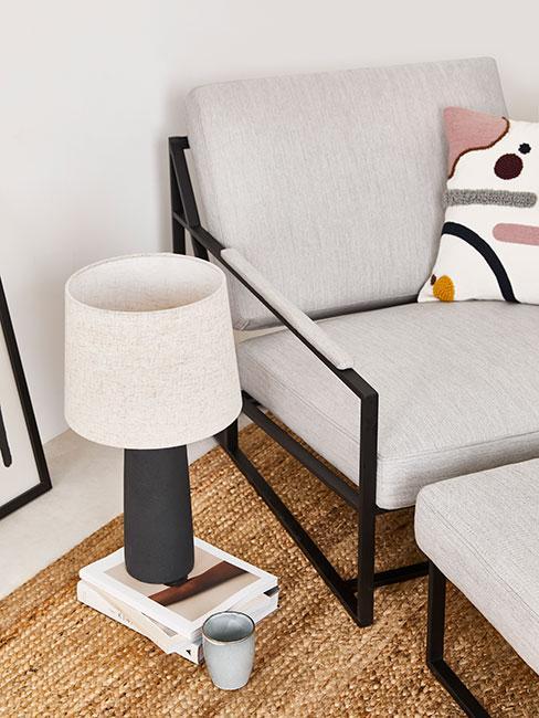 Niski szary fotel z ponóżkiem w jasnym pokoju z ksążkami i lampą z czarnego drewna i lnu na dywanie z trawy morskiej