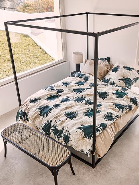 Carne łóżko z baldachimem w jasnej sypialni z czarną ławką z plecionką wiedeńską i pościelą w liście palm