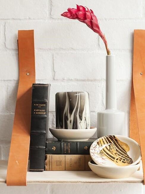 Fragment półki z książką, białym wazonem z kwiatem oraz świecą w marmurkowy wzór