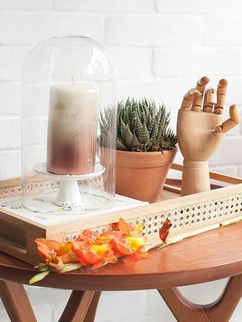 Świece ombre na tacydekoracynej obok kaktusa i drewnianej dekoracji w kształce ręki