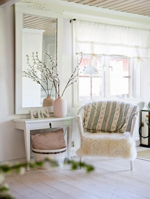 Biały przedpokój z bielonym stoliczkiem z wazonem, fotelem oraz lustem na ścianie