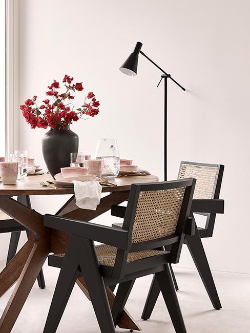 okrągły stół do jadalni z brązowego drewna otoczony czarnymi drewnianymi krzesłami z plecionką wiedeńską z czarnym wazonem z kamionki na stole