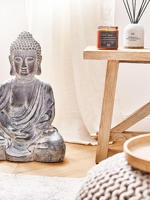 Statuetka buddy z kaminia w jasnym salonie obok drewnianego stołka z świeczką i dyfuzorem zapachowym