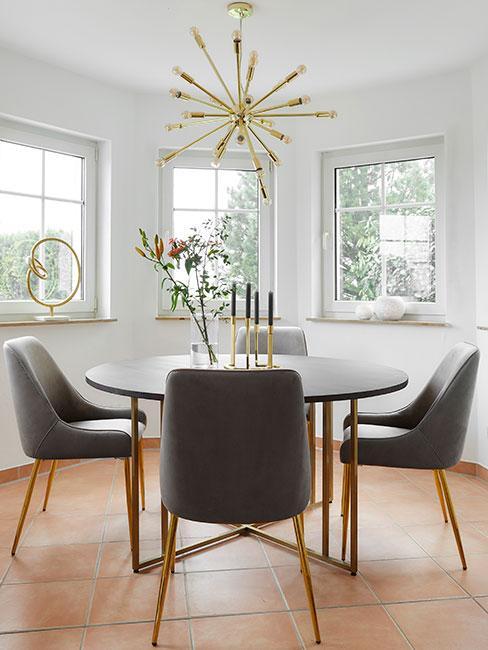 okrągły stół z ciemniego drewna otoczony tapicerowanymi krzesłami z szarego aksamitu w w jadalni z dużymi oknami i wiszącą złotą lampą typu gwiazda