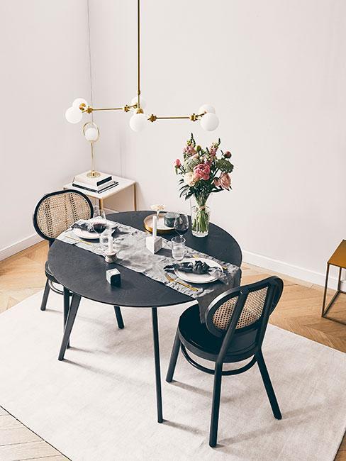 czarnyy okrągły stół do jadalni z czarnymi zaokrągłymi krzesłami z plecionką wiedeńską pod dwuramienną złotą łampą